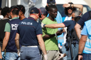 Migrants fouillés par des policiers italiens à leur débarquement sur le port de Pozzallo, en Sicile, le 7 juin.