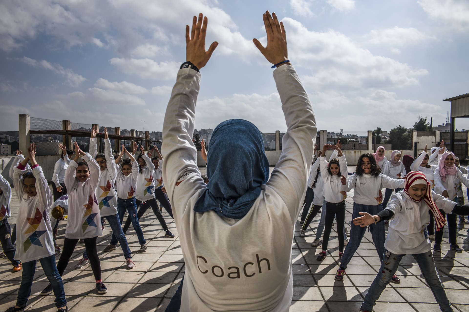 Avec l'association, Haneen Al-Khateeb parcourt le pays, ballons sous le bras. Ce 17 novembre, à Amman, les ateliers qu'elle donne avec plusieurs autres coaches ont attiré une cinquantaine de filles de l'école Oum Baia. Alors que le sport est une matière négligée pour les filles en milieu scolaire, Madrasati s'attache à leur donner l'opportunité de s'essayer au football, au basket, au handball.