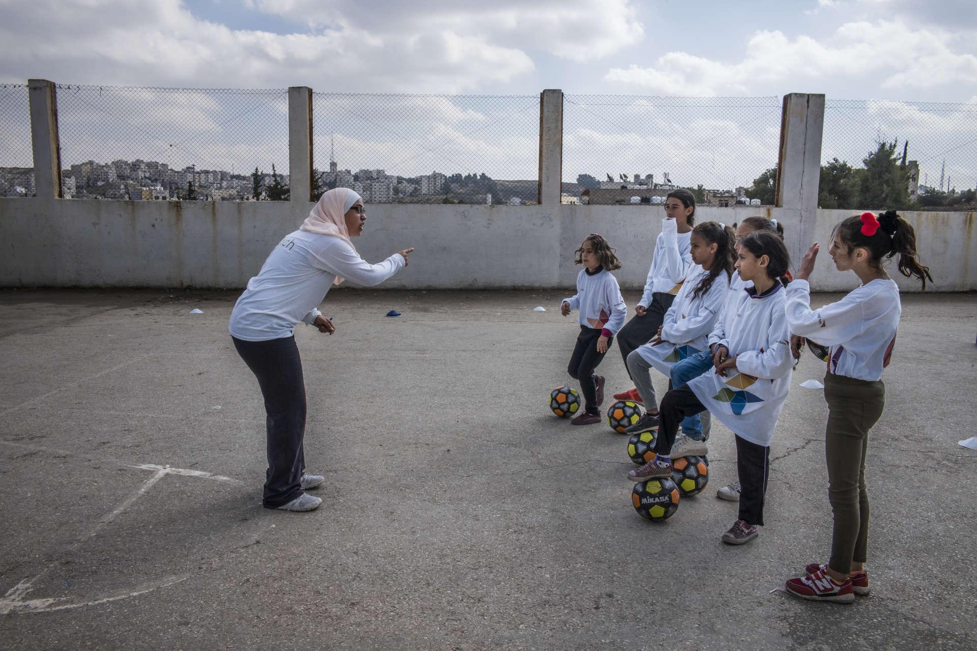 """Bénéficiant de l'initiative Madrasati (mon école), lancée en 2008 etvisant à améliorer les conditions d'apprentissage physique et éducatif, de jeunesfilles ont l'opportunité de pratiquer un sport dans une société qui ne leur en donne pas assez souvent l'occasion. """"Les filles ont autant le droit de jouer au football que les garçons"""", commente Rahaf, la jeune coach de l'association. Le 17 novembre 2018."""