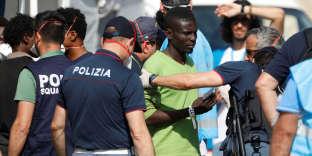 Migrants fouillés par des policiers italiens à leur débarquement sur le port de Pozzallo, en Sicile, le 7 juin.