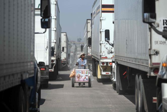 Un vendeur ambulant circule entre les camions de marchandises qui attendent de passer la frontière, à Tijuana (Mexique), le 6 juin.