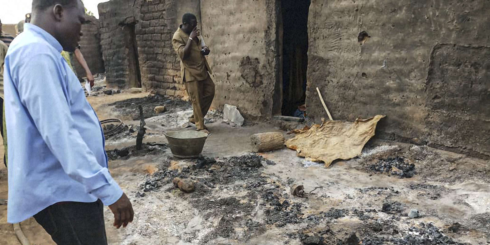 Officials and residents stand near ashes on June 11, 2019 in the Dogon village of Sobane-Kou, near Sangha, after an attack that killed over 100 ethnic Dogon on June 9, 2019 evening. The attack came less than three months after nearly 160 members of the Fulani ethnic group were slaughtered by a group identified as Dogon. / AFP / STRINGER