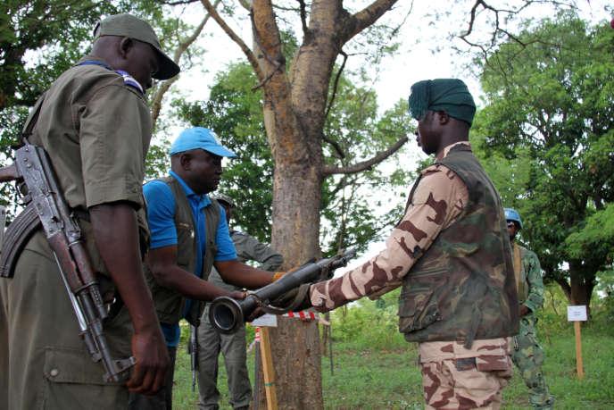 Un membre du groupe armé RJ Sayo remet symboliquement son arme aux techniciens chargés du désarmement,à la sortie de Paoua, dans l'ouest de la Centrafrique, le 30 mai 2019.
