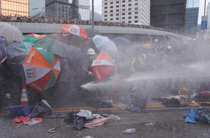 La police utilise des canons à eaux pour disperser les manifestants, mercredi 12 juin, à Hongkong.