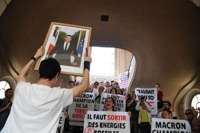 Un homme brandit le portrait d'Emmanuel Macron, fraîchement décroché à Paris, le 24mai.