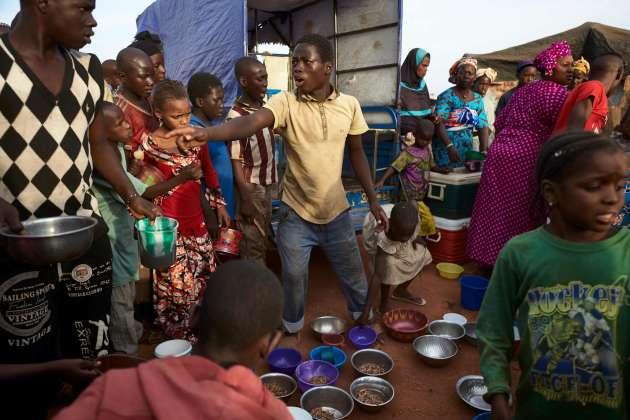 18 mai 2019. Des enfants attendent la distribution d'eau et de nourrituredans le camp de déplacés de Faladié, prés de Bamako, où 800 Peuls se sont installés sur une décharge, après avoir fui les violences intercommunautaires du centre du Mali.