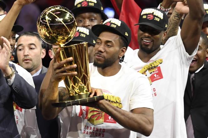 L'ailier Kawhi Leonard brandit le trophée NBA après la victoire de Toronto face aux Golden State Warriors, à Oakland, le 13 juin.