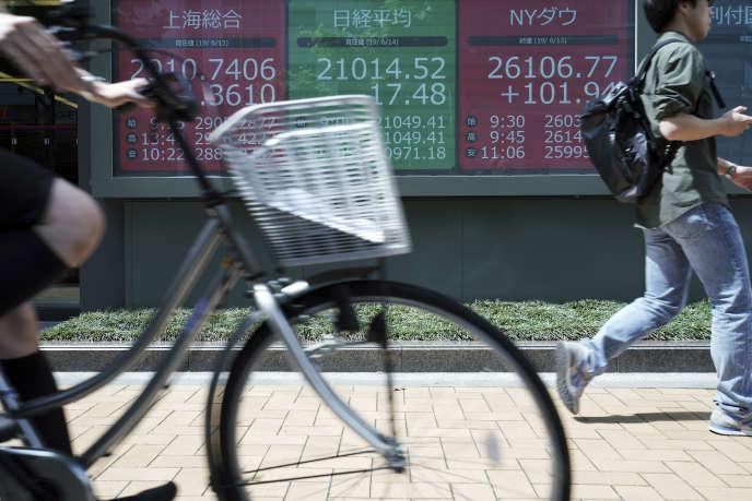 Panneaux indiquant la valeur des indices boursiers, le 14 juin à Tokyo.