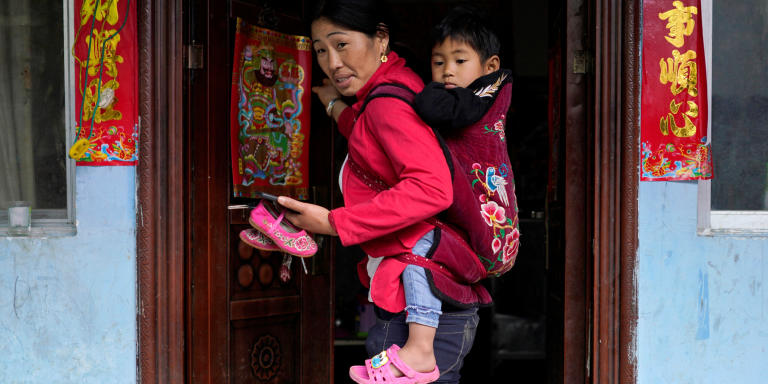 Cha Huilan, a 40-year old Lisu woman, carries her daughter in her home in Lazimi village in Nujiang Lisu Autonomous Prefecture in Yunnan province, China, March 24, 2018. Picture taken March 24, 2018. REUTERS/Aly Song - RC12EA15DD00
