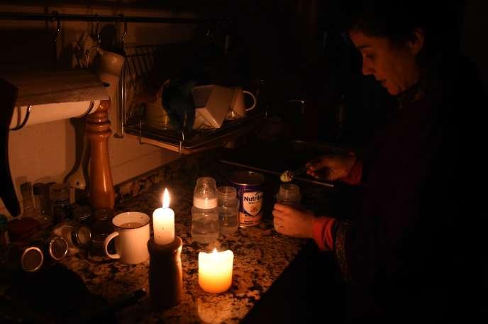 Un femme prépare un biberon à la lueur de bougies à Montevideo (Uruguay), le 16 juin.