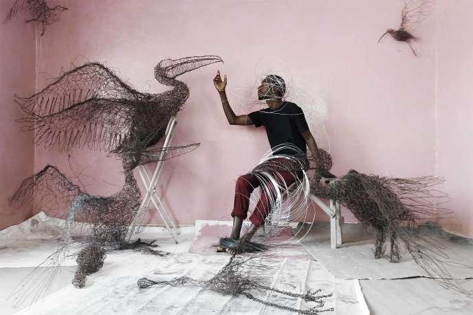 Portrait d'Oumar Ball, sculpteur (République islamique de Mauritanie) : malgré la pression sociale, Oumar – qui représente des ombres – a exposé à la Biennale de Dakar et continue de sculpter des oiseaux géants dans la banlieue de Nouakchott, enattendant le bon moment pour prendre son envol.