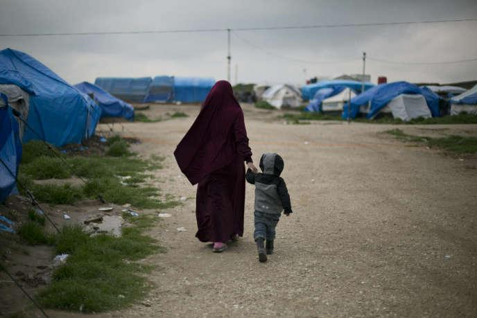 Samira, un ressortissant belge marié à Français un membre de l'Etat islamique, Karam El-Harchaoui, marche avec leur fils au Camp Roj dans le nord de la Syrie le 27 mars.