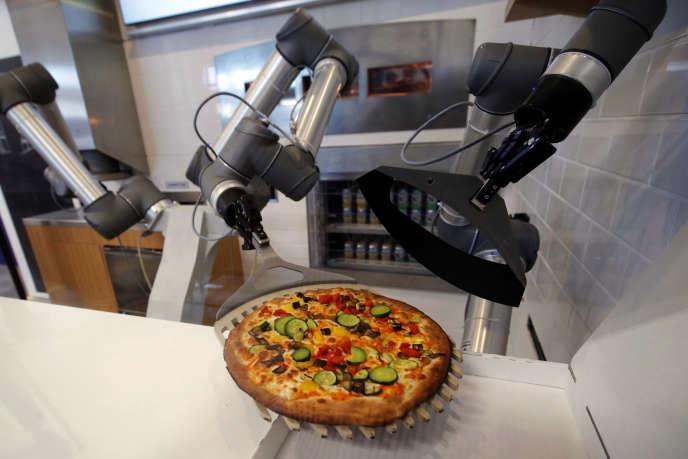 Un robot pizzaiolo prépare une pizza, au showroomde lastart-upfrançaiseEkim, àMontévrain (Seine-et-Marne), en juin 2018.