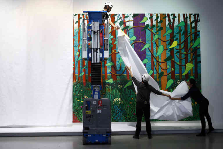 Workers remove the protections as renowned British painter David Hockney poses during the unveiling of a huge painting he is donating to the Pompidou Center in Paris,