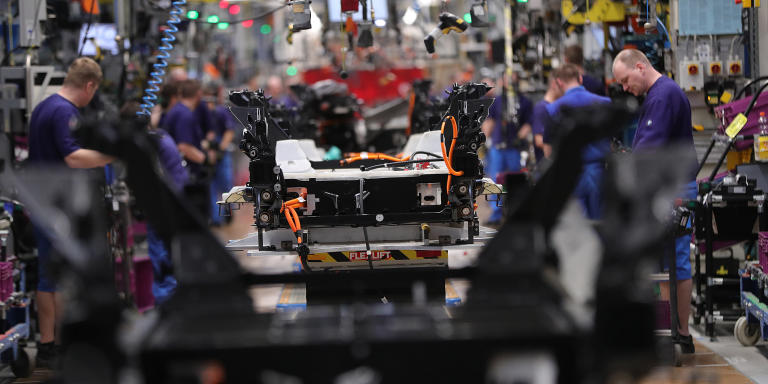 Employees work on BMW i3 electric automobile chassis fitted with battery packs on the assembly line at the Bayerische Motoren Werke AG factory in Leipzig, Germany, on Thursday, March 14, 2019. Chancellor Angela Merkel's plan to hatch a German battery-cell industry from scratch is gaining momentum as Europe's biggest economy tries to lower emissions while keeping Chinese automobile competition at bay. Photographer: Krisztian Bocsi/Bloomberg via Getty Images