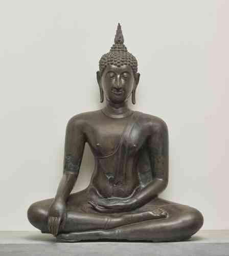 """«En effleurant le sol de sa main droite, le Bouddha prend la Terre à témoin des innombrables mérites accumulés au cours de ses vies antérieures. Précédant de peu le temps de l'éveil, l'épisode est ici transcrit avec toute la science de l'ellipse si fréquente dans les arts asiatiques. Le corps et le visage aux caractéristiques surprenantes transcrivent certains des signes distinctifs du """"Grand Etre"""" qu'était le Bouddha: protubérance crânienne, torse puissant, doigts souples et effilés tels les pétales d'une fleur de lotus.»"""