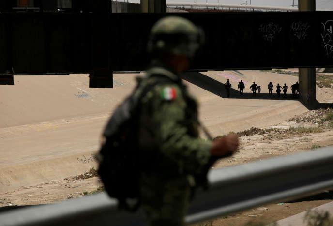 Un membre de la garde nationale mexicaine regarde depuisCiudad Juarez (Mexique) des migrants marcher à El Paso (Texas) après qu'ils ontillégalement traversé la frontière, le 21 juin.