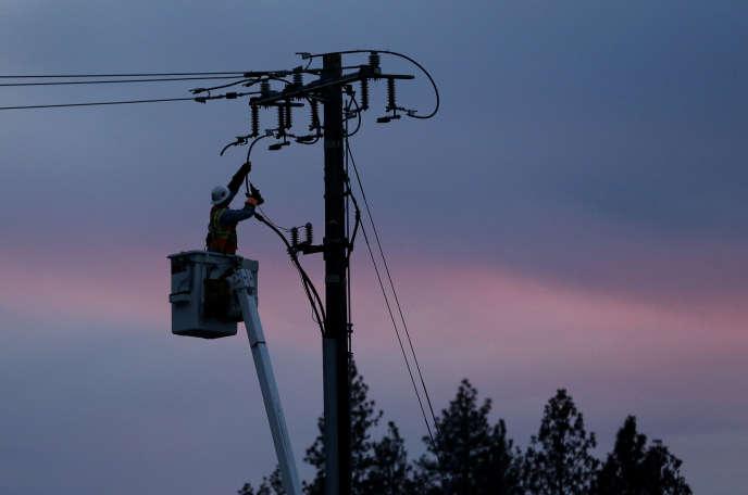 Le 26 novembre 2018, un monteur de lignes Pacific Gas & Electric travaille à la réparation d'une ligne électrique à Paradise, en Californie, ravagé par les incendies.
