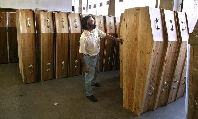 Un employé des pompes funèbres générales de la Ville de Paris vérifie, le 20 août 2003, la finition de cercueils, alors que la canicule a occasionné des milliers de décès supplémentaires.