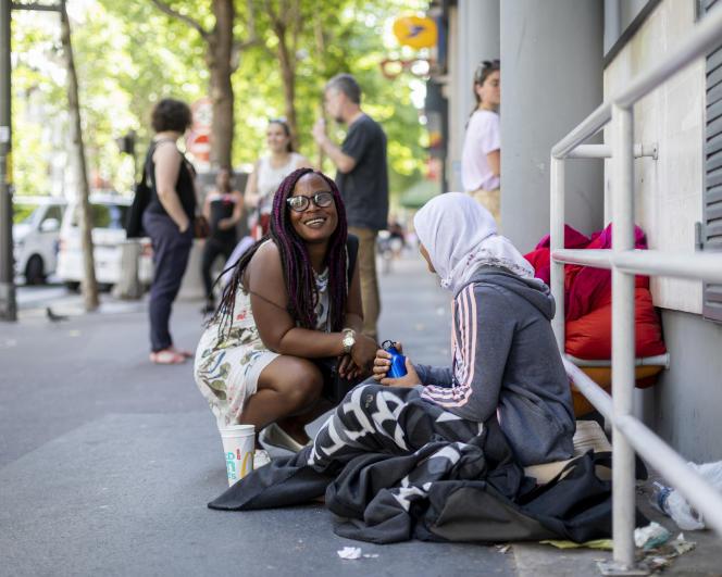Prisca Pkan, bénévole de l'ADSF, profite de sa maraude pour distribuer de l'eau et des lingettes à une femme SDF, à Paris, le 27 juin.