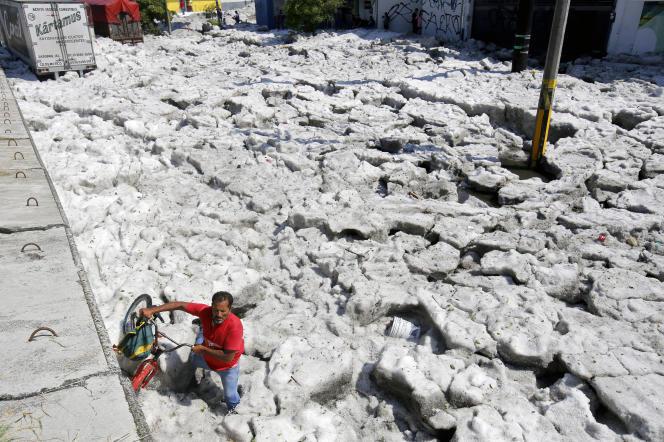 Un homme tente de se frayer un chemin à travers la glace, avec son vélo.