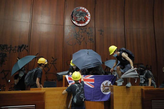 Des manifestants brandissent un drapeau colonial hongkongais et défigurent le logo de HongKong à la chambre législative, le 1er juillet.