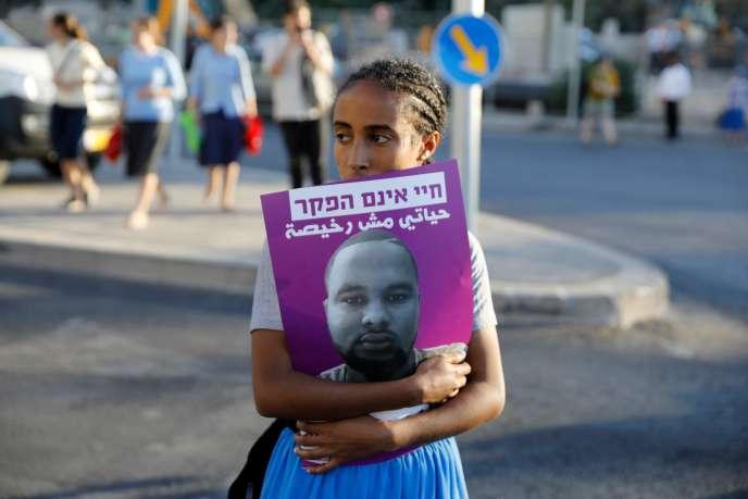 Une jeune Israélienne porte dans ses bras une affiche du portrait de Solomon Tekah– abattu dimanche par un policier en civil–en marge d'une manifestation contre les forces de l'ordre, le 2 juillet à Jérusalem.