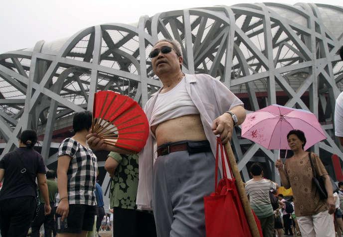 Un homme avec le t-shirt relevésort du stade national de Pékin, en Chine, en août 2009.