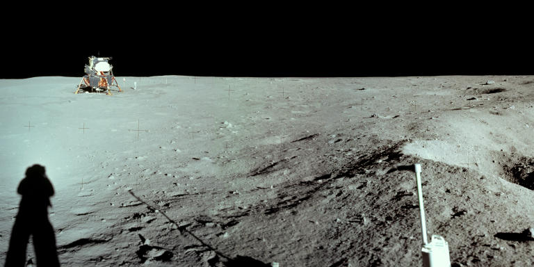 This photograph of the Lunar Module at Tranquility Base was taken by Neil Armstrong during the Apollo 11 mission, from the rim of Little West Crater on the lunar surface. Armstrong's shadow and the shadow of the camera are visible in the foreground. When he took this picture, Armstrong was clearly standing above the level of the Lunar Module's footpads. Darkened tracks lead leftward to the deployment area of the Early Apollo Surface Experiments Package (EASEP) and rightward to the TV camera.  This is the furthest distance from the lunar module traveled by either astronaut while on the moon.
