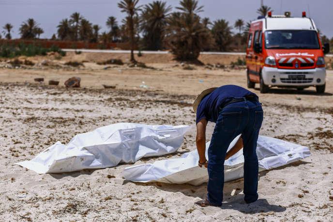 Un membre du Croissant-Rouge tunisien récupère des corps de migrants échoués au sud de l'île de Djerba, le 6 juillet 2019.