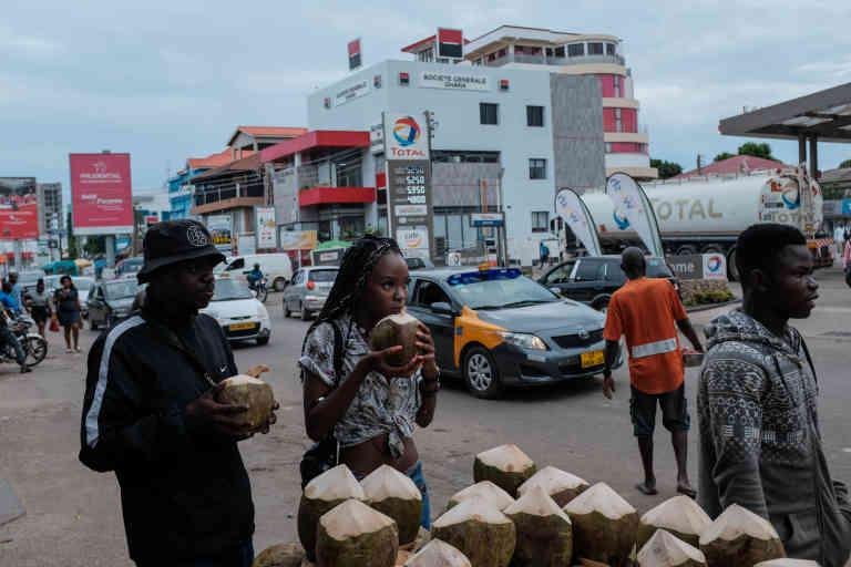 Customers enjoy coconuts on Oxford Street in Osu. May 16, 2019. Ghana. Photo: Francis Kokoroko @accraphoto