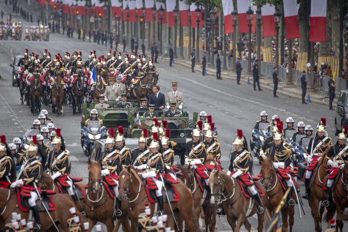 Emmanuel Macron remonte les Champs-Elysées sous les applaudissements mêlés aux sifflements du public, le 14 juillet, à Paris.