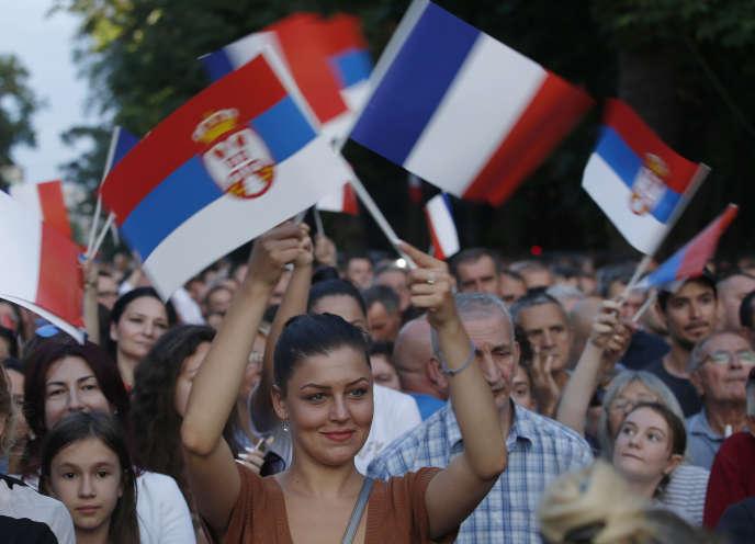 Une femme agite des drapeaux serbe et français à Belgrade, en Serbie, le 15 juillet.