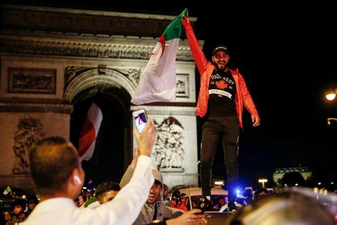 Devant l'Arc de triomphe, le 14 juillet 2019, à Paris, un supporteur fête la qualification de l'Algérie à la finale de la Coupe d'Afrique des nations.
