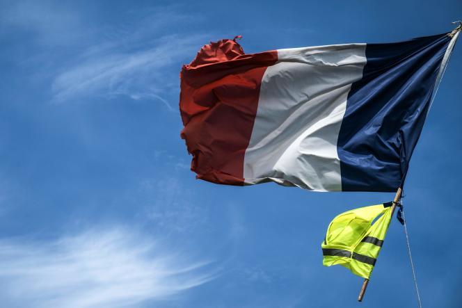 Un gilet jaune flotte avec le drapeau français, le 23 juin à Bourg-Achard (Eure).