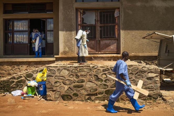 Des employés de la morgue désinfectent l'entrée du bâtiment à Beni, en RDC, le 14 juillet.