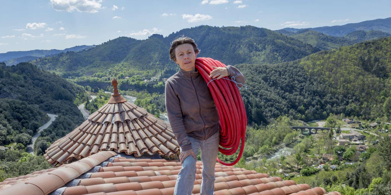 Patricia Demangeon sur le toit de son chateau avec un rouleau de tube PER gainé pour l'alimentation en eau chaude de la pièce en dessous. Chateau de Hautsegur, Meyras, France 30/04/2019.