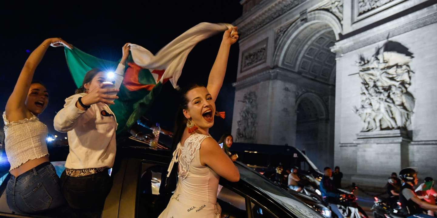 Algeria's supporters waves Algeria's national flag as they celebrate in front of the Arc de Triomphe on the Champs Elysee Avenue in Paris, after Algeria won 1-0 the 2019 Africa Cup of Nations (CAN) final football match between Algeria and Senegal, on July 19, 2019. / AFP / Bertrand GUAY