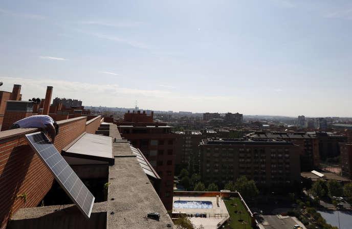 L'architecte espagnolInaki Alonso installe un panneau solaire sur son toit-terrasse, à Madrid, le 9 septembre 2014.