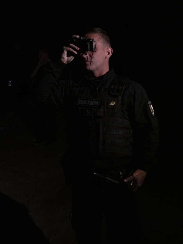 Un officier de la gendarmerie mobile utilise une paire de jumelle à vision nocturne lors d'une patrouille à Calais.