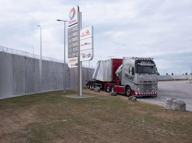 La station d'essence Total s'est équipée d'un mur anti-intrusion de 5 mètres de haut et de barbelés pour éviter les passagers clandestins dans les camions vers l'Angleterre.
