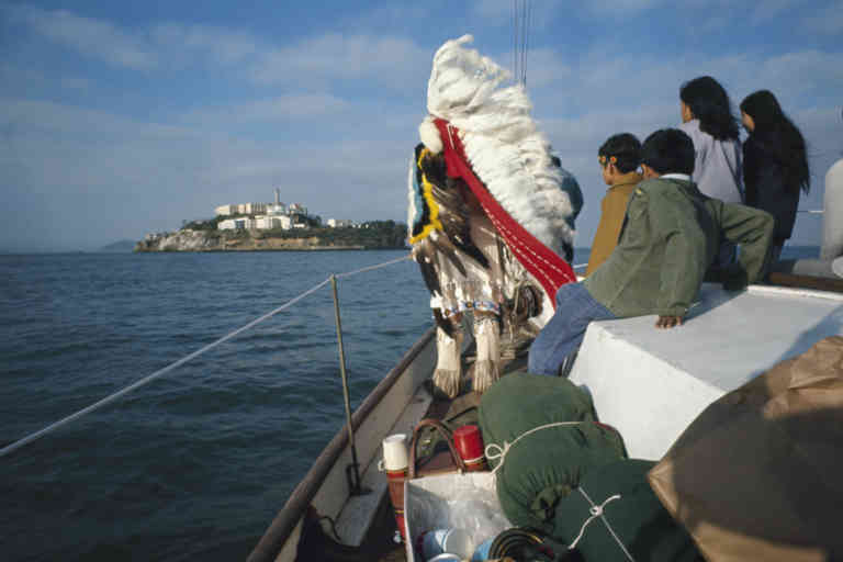 View along the gunwale of a boat shows group of Native Americans, one named Tim Williams (a chief of the Klamath River Hurek tribe) in full headdress and ceremonial attire, as they approach Alcatraz Island with the intention of reclaiming it from the US government, San Francisco, California, late 1969 or early 1970. For almost 19 months months, a group of Native Americans, under the name 'Indians of all Nations,' occupied the island, which at the time was out of service as a Federal Prison, based on their interpration of a treaty which they believed granted them the right to reclaim any land originally theirs sold to and subsequently abandoned by the US government. (Photo by Ralph Crane/The LIFE Picture Collection via Getty Images/Getty Images)