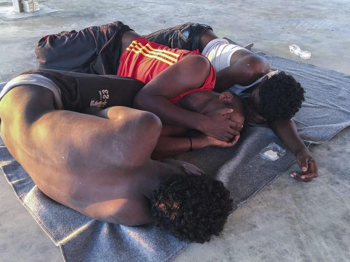 Des migrants secourus se reposent sur une côte, à environ 100 kilomètres à l'est de Tripoli, en Libye, le 25 juillet.