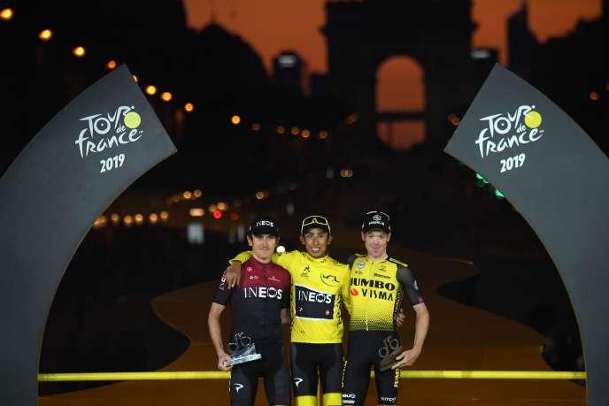 Egan Bernal, de l'équipe Ineos, vainqueur du Tour de France 2019, entouré à sa droite de son coéquiper Geraint Thomas, classé deuxième, et de Steven Kruijswijk (Jumbo-Visma), qui termine troisième.