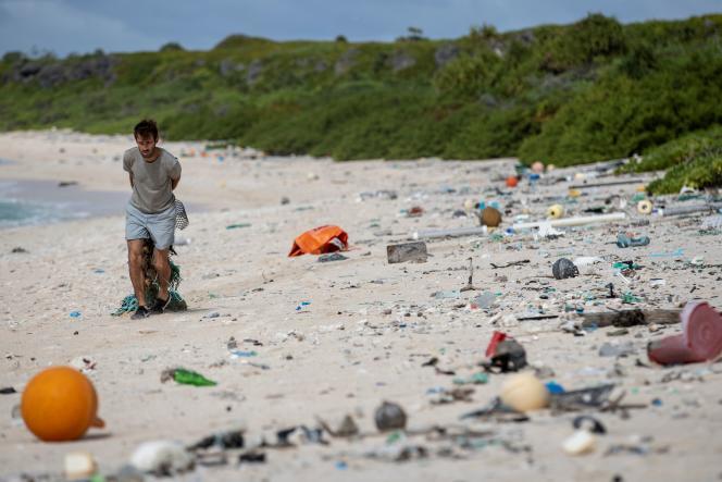 Le 14 juin, un membre de l'équipe de nettoyage des plages ramasse des ordures sur l'île Henderson, dans l'océan Pacifique.