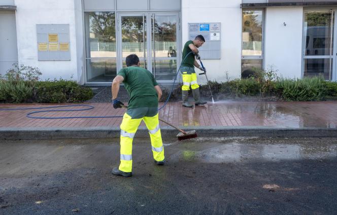 Des employés municipaux nettoient le trottoir devant la permanence dela députée Monique Iborra à Tournefeuille, près de Toulouse, le 2 août 2019.