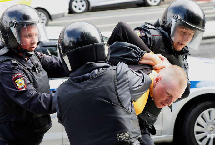 Des policiers anti-émeute arrêtent un participant à un rassemblement non autorisé appelant à des élections équitables, à Moscou, le 3 août.