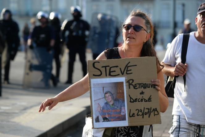 Une femme tient une photo de feu Steve Maia Canico, lors d'un rassemblement à la mémoire du jeune homme, à Nantes, le 3 août.