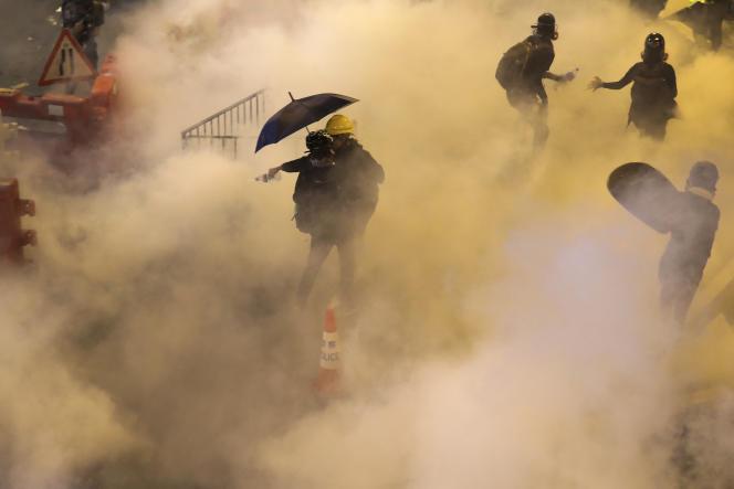 Des manifestants sous les gaz lacrymogènes tirés par des policiers, à Causeway Bay, àHongkong, le 4août.
