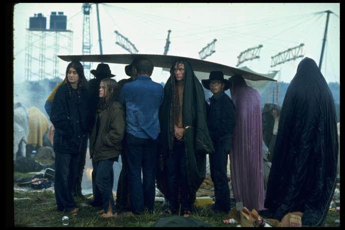 A Woodstock, des festivaliers se protègent de la pluie grâce à une planche de bois.